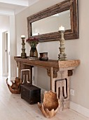 Bowl-like, wooden objets d'art and trunk on floor below candlesticks on rustic antique console table and framed mirror on wall