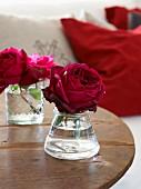 Romantisch rote Rosen in Glasväschen auf rustikalem Holztisch