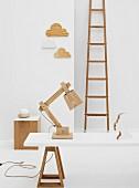 Holzobjekte in weißem Raum - Tischlampe aus Holz Bauteilen auf weisser Tischplatte mit Böcken vor Wand mit Deko-Objekten und Vintage Leiter