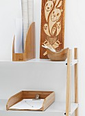 Wooden objects in white surroundings - half-height shelving with white metal shelves and wooden office furnishings next to wooden panel carved with animal motifs