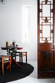 Tea service on simple dining table with stools on round rug next to antique, carved wooden panel with glass panes