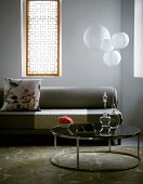 Retro-style, round side table in front of grey sofa and windows with Oriental-style screens flanking spherical pendant lamps