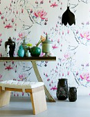 Stool with cushion and various china containers on partially visible table against wallpaper with stylised floral pattern
