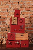 Stacked boxes, some painted rust red, with attached components against rustic brick wall