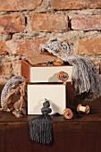 Gestapelte Kisten mit weissen Fronten und Kurzwarenartikeln auf Holzkommode vor rustikaler Ziegelwand
