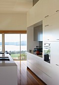 Modern kitchen with white cupboards and sink in central island