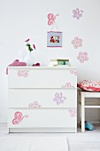 Colourful decals on simple, white chest of drawers and wall