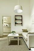 Weisser Couchtisch auf Teppich vor heller Sofakombination und schlichte Hängeleuchte in reduziertem Wohnzimmer, im Hintergrund Durchgang zur Küche