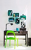 Work area with desk and bright green chair below plastic storage boxes mounted on wall