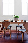 Tea service on wooden table and curved, laminated timber chairs with grey felt seats