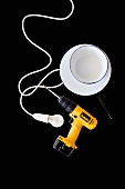 Yellow cordless drill, light bulb, electrical cable and white enamel bowls on black surface