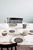 Hand-painted crockery in black and white on vintage table