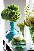 Various flowers in glass vases and blue ceramic vase