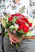 Hands holding bouquet with red roses