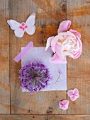 Flowers and paper butterfly on wooden surface