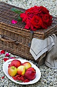 Plate of fruit next to red roses on picnic basket