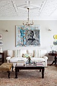 Antique upholstered footstool and coffee table in front of pale sofa below modern artwork on wall in traditional interior with stucco ceiling
