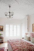 Double bed with floral blanket and pendant lamp with glass lampshades hanging from stucco ceiling
