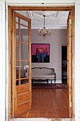 View though open door of Rococo-style bench below modern picture on wall
