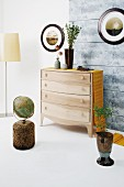 Wooden chest of drawers with yellow runner surrounded by objets d'art with natural motifs