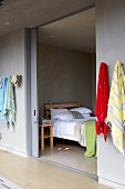 Colourful beach towels hanging on corridor wall and view into bedroom with double bed through open sliding door