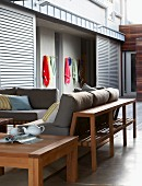 Wooden furniture with grey cushions on terrace of modern, South African beach house; view of beach towels on wall rack through open sliding doors