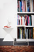 White bookcase, white, retro side table and worn, white metal chair