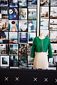 Tailors' dummy wearing green lady's jacket in front of colourful wall of photographs