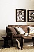 Braun gestreiftes Sofa mit Beistelltischen und selbstgebastelte Wandlampen in Bilderrahmen