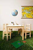 Hand-crafted globe lampshade above children's table on artificial grass carpet