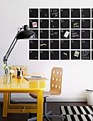 Yellow-painted desk and black retro lamp in front of calendar board with memoranda