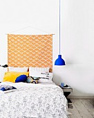 Hand-crafted wall hanging on white wall above comfortable double bed