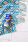Spray can on blue-patterned, fringed fabric