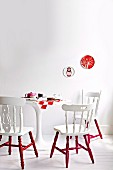 Old wooden chairs painted white and red around set, round, white table on white wooden floor against white wall