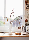 Jewellery hanging on twig in white vase on window sill
