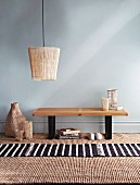 Hand-crafted lampshade made from bamboo place mat above small wooden table against blank wall; sisal carpet and striped rug on floor