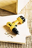 Gelber Akkuschrauber liegt auf zugeschnittenen Sperrholzplatten