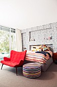 Red lounge chair and pouffe at foot of bed against wall with ornate wallpaper in modern bedroom with retro atmosphere