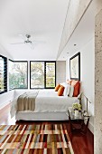 Patchwork rug in front of double bed in contemporary bedroom with row of windows