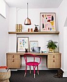Retro-style home office in niche with pink armchair