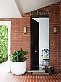Überdachter Eingangsbereich in Klinkerfassade mit Durchgang zum Garten; geöffnete Eingangstür gewährt Einblick ins Haus