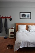 Artistic photo over custom-made bed with wooden headboard in grey-painted bedroom; coat rack to one side