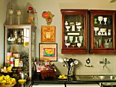 Collection of antique crockery in antique display cabinets on wall above kitchen counter in corner