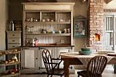 Grosser, alter Geschirrschrank, Schubladenkommode und Armlehnstühle im Shakerstil als stilvolle Einrichtung in ehemaliger, umgebauter Milchfarm