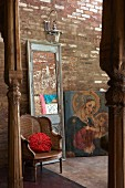 Antique cane armchair, mirror with vintage, wooden frame and painting of the Madonna in front of rustic brick wall; carved wooden pillars in foreground