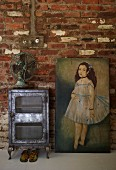Vintage fan on antique, metal cabinet and oil painting against rustic brick wall in living area