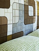 Fine leather patchwork in contrasting natural colours at head of double bed; pillows with pattern of small, green circles
