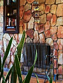 Stone wall with metal fire screen, shelves in niche and ornaments on miniature, wall-mounted shelves; Sansevieria in foreground