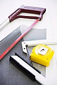 Red hacksaw, grey mesh, yellow tape measure and pieces of metal frame on white worksurface