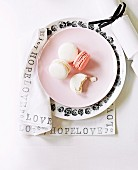 Place setting with macaroons on pink dessert plate and black and white floral plate on napkin printed with black lettering